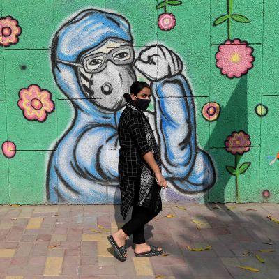 Kvinna promenerar på en gata i New Delhi, Indien