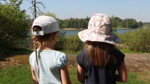 Två flickor iklädda hatt och keps står och blickar ut över havet vid daghemmet Tallbo.