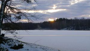 Aurinko laskee talvella järvenrannan taakse.