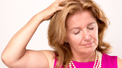 Kvinna med pärlhalsband håller sig för huvudet och blundar