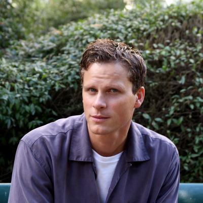 Skådespelaren Adam Pålsson sitter på en bänk i ett grönområde och tittar in i kameran. Han har en ljusblå tröja på sig.