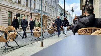 Flera par kommer vandrande emot på en gågata i Vilnius i Litauen med coronasäkerhetsavstånd mellan paren.