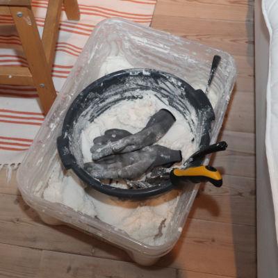 Vitt pulver, som är amfetamin, i en plastlåda på ett trägolv.