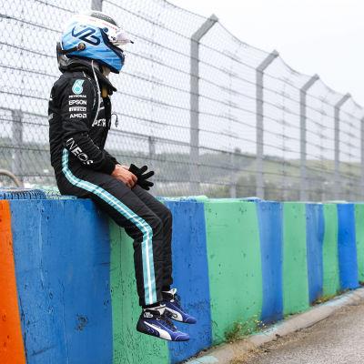 Valtteri Bottas sitter på kantvägg.