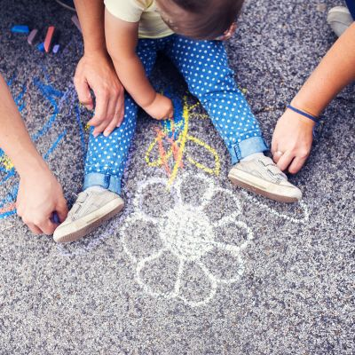 Barn som ritar på asfalt