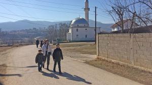 Två pojkar och en kvinna går på en väg. I bakgrunden syns en moské.