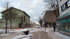 En snöbeklädd gågata.På sidorna syns olika byggnader med affärer i bottenplan.
