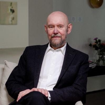 Esko sitter i en svart kostym i en fåtölj i ett vitt rum. I bakgrunden syns talvor på väggen, blommor i en vas och en släckt lampa i mässing.