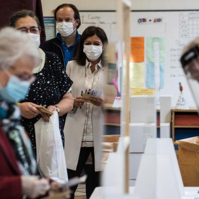 Socialistiska partiets Anne Hidalgo står och köar för att få rösta i lokalvalet i Frankrike. Hon är klädd i beige jacka och framför henne står en äldre dam med blått munskydd.