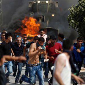 Unga palestinier springer från israeliska säkerhetsstyrkor.