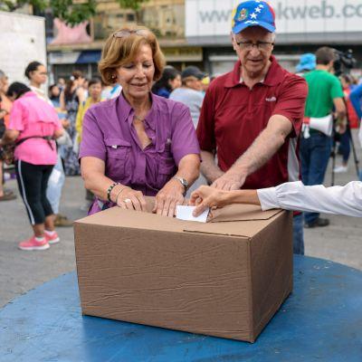 Väljare lägger sina röstsedlar i en papplåda i Caracas 16.7.2017.