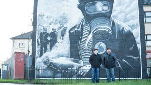 Miehet seisovat seinämaalauksen edessä