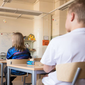 Fyra elever och en lärare sitter i ett klassrum.
