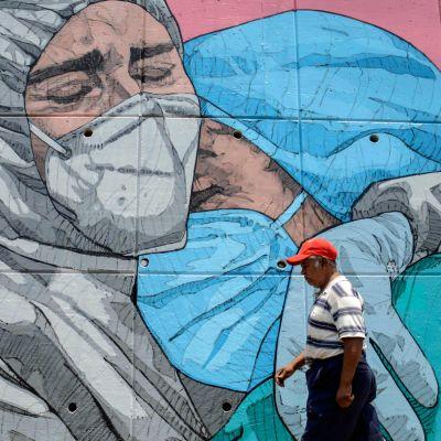 En man går förbi en väggmålning av två sjukskötare som kramar varandra i Mexiko.