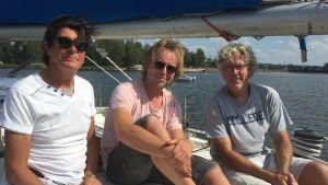 Tre män som sitter på en segelbåt.