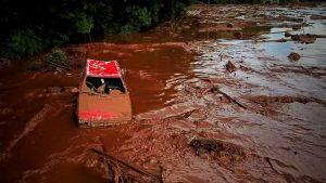 En röd sönderslagen bil har dragits med de bruna lermassorna.