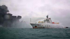 Räddningsbåt på havet i närheten av den brinnande oljetankern.