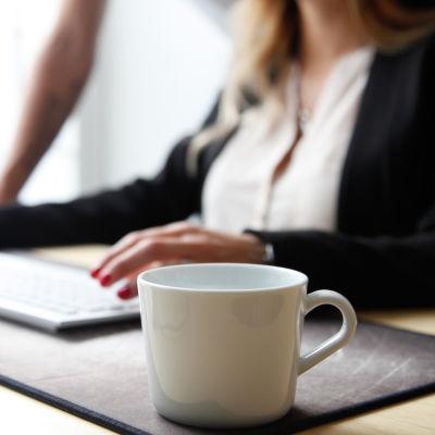 Kaffekopp i förgrunden, människa som skriver på dator i bakgrunden