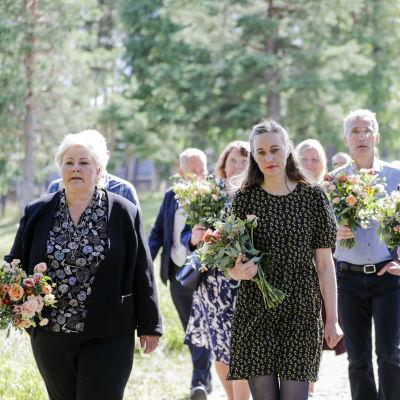 Erna Solberg ja muista muistojuhlaan osallistuneita kukkakimput kädessään.
