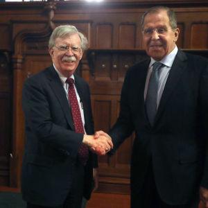 John Bolton och Sergej Lavrov skakar hand.