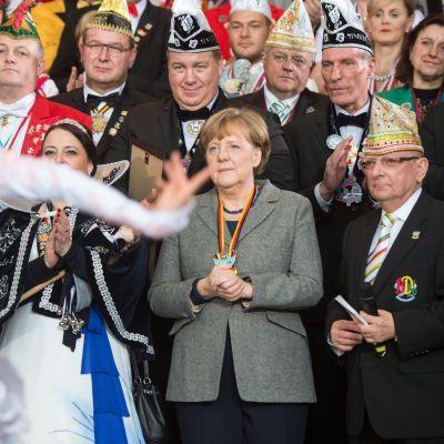 Angela Merkel seuraa tanssiesitystä.