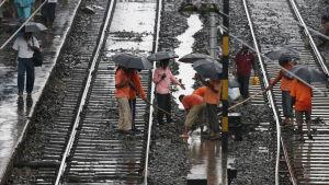 Tågskenor rengörs efter häftiga monsunregn i Indien i augusti 2015.