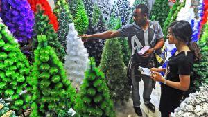 En nigeriansk affärsman köper konstgjorda julgranar på marknaden i Yiwu i Kina.
