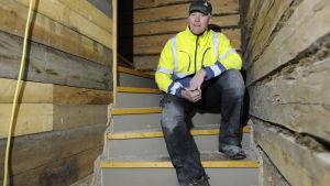 Tony Stenfors i reflexjacka och skärmmössa sitter i en trappa i ett gammalt hus
