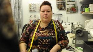 Erica Wickman sitter med måttband runt nacken i sin kombinerade syateljé och klädbutik