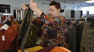 Erica Wickman viker en tröja i sin butik
