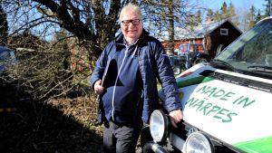 Raymond Wesander, med kalendern under armen, står lutad mot sin bil och njuter av majsolen