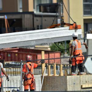 En byggarbetsplats där tre män styr en komponent som hänger från en lyftkran.