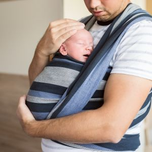 En pappa vars ansikte inte syns håller ett barn mot sitt bröst.