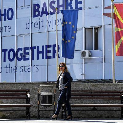 Kaksi naista kävelee kadulla. Taustalla Pohjois-Makedonian ja EU:n liput.