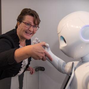 Riitta Bekkhus kättelee robottia.