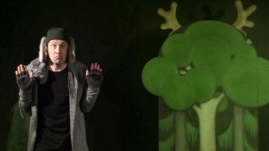 En skådespelare i grå rock och stora lurviga hundöron hängande från mössan håller upp händerna.
