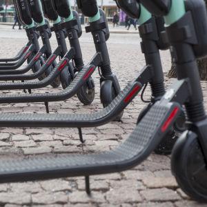 En rad parkerade elsparkcyklar framför Kiasma.