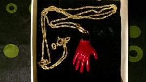 Röd hand-smycke. Har att göra med Nick Caves Red Right Hand