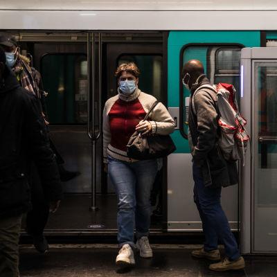 Passagerare kommer ut ur en metro i Paris. De har munskydd på sig.