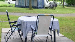 ETt bord med duk och två stolar ute på en campingplats.