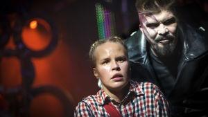 Riddar Kato ( Mika Fagerudd) hotar och hånar den skräckslagna  Mio ( Malin Olkkola)