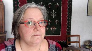 Eva Sjöström, en dam med grånande hår och glasögon med röda skalmar.