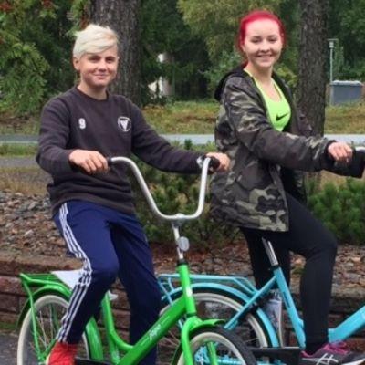 Teini-ikäiset poika ja tyttö ajavat vihreällä ja sinisellä jopolla