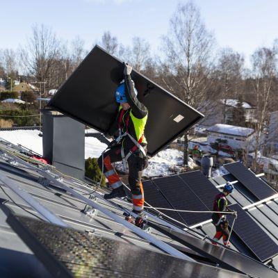 Solarvoima Oy:n asentaja Joni Särkinen kantaa aurinkopaneeleja omakotitalon katolle.