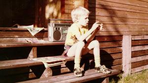 Jouni Järvelä istuu alle kymmenvuotiaana mökin portailla sarjakuvalehden ja kasettinauhurin kanssa.