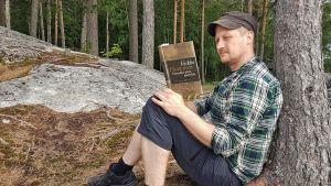 Bloggari Marko Rossi lukee Havukka-ahon ajattelijaa kalliolla.
