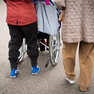 Nainen työntää vanhusta pyörätuolissa olevaa vanhusta.