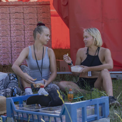 Kolme nuorta naista istuu varjossa syöden eväitään.