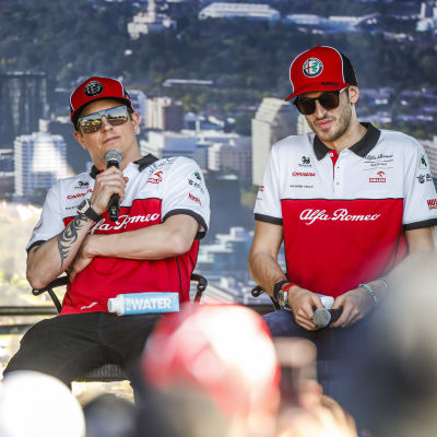 Kimi Räikkönen och Antonio Giovinazzi sitter på en scen.