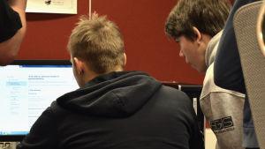 Två ungdomar sitter med ryggen mot kameran vid en dator i en skola